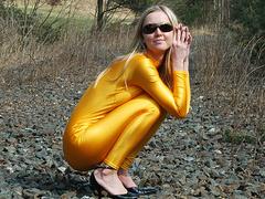 Fetish blonde whore in nylon suit porsing outdoors