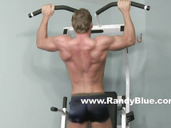 Muscled gay Danny Harper working hard out in gym
